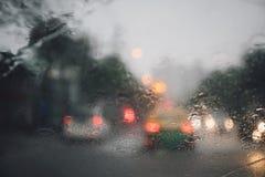 Descensos de la llovizna de la lluvia en el parabrisas de cristal en la tarde Calle en las fuertes lluvias fotos de archivo libres de regalías