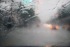 Descensos de la llovizna de la lluvia en el parabrisas de cristal en la tarde Calle en las fuertes lluvias imágenes de archivo libres de regalías
