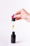 Descensos de un dropper en una botella Aislado en un fondo blanco Farmacia y fondo sano medicina fotografía de archivo libre de regalías