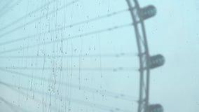 Descensos del agua de lluvia en el vidrio de la ventana con el fondo de la noria almacen de metraje de vídeo