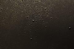 descensos del agua en backgroun negro imagen de archivo