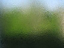 Descensos del agua en cierre transparente verde del vidrio para arriba Imagenes de archivo