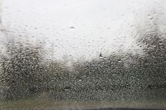 Descensos del agua en el parabrisas de un coche foto de archivo