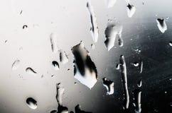 Descensos del agua en el vidrio de la ventana con un modelo interesante Foto de archivo libre de regalías