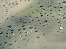 Descensos del agua en la superficie de cristal como fondo Imagen de archivo