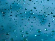 Descensos del agua en la superficie de cristal como fondo Imagenes de archivo