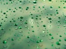 Descensos del agua en la superficie de cristal como fondo Foto de archivo libre de regalías