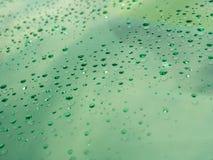 Descensos del agua en la superficie de cristal como fondo Imágenes de archivo libres de regalías