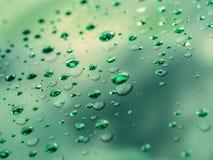 Descensos del agua en la superficie de cristal como fondo Fotografía de archivo libre de regalías