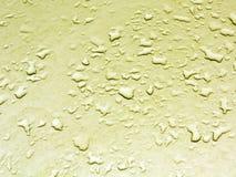 Descensos del agua en superficie de metal amarilla del coche Fotografía de archivo