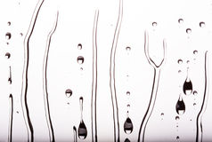 Descensos del agua que fluyen abajo del vidrio, blancos y negros Imagen de archivo libre de regalías