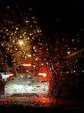 Descensos del agua sobre el vidrio del coche en el fondo colorido de las luces en la noche fotografía de archivo