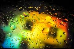 Descensos del agua sobre el vidrio delante del fondo colorido imagenes de archivo