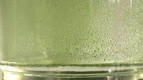 Descensos del goteo puro del agua o del alcohol dentro de un tarro de cristal, en fondo verde El proceso destilador Primer almacen de video