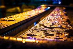 Descensos después de la lluvia en el banco en la noche que riela teniendo en cuenta las lámparas con el fondo del bokeh Fotografía de archivo