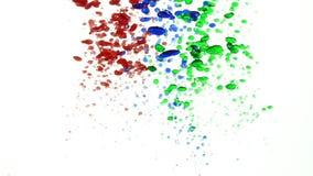 Descensos multicolores del aceite en el agua que vierte abajo de respaldo entonces de levantamiento a la cámara lenta superior metrajes