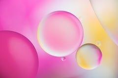 Descensos rosados de las burbujas del aceite y de aire en el agua Foto de archivo libre de regalías