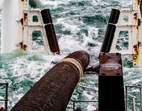 Descent of the pipeline to a bottom exhausting with the pipelaying barge. Installation of the underwater gas pipeline.  Royalty Free Stock Photography