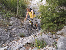 Descent to a mountain bicycle. The man goes down from mountains on a bicycle Stock Images