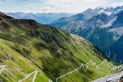 Descida íngreme da passagem de Stelvio da estrada da montanha, em cumes italianos imagens de stock royalty free