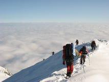 Descida abaixo do pico de montanha nevado Fotos de Stock Royalty Free