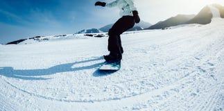 Descida da snowboarding do Snowboard na inclinação na estância de esqui Foto de Stock