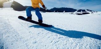 Descida da snowboarding do Snowboarder na inclinação de montanha do inverno Fotos de Stock