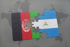 desconcierte con la bandera nacional de Afganistán y de Nicaragua en un fondo del mapa del mundo Fotografía de archivo
