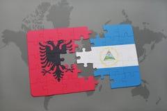 desconcierte con la bandera nacional de Albania y de Nicaragua en un mapa del mundo Foto de archivo
