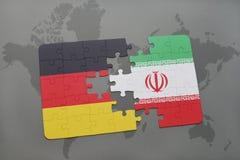 desconcierte con la bandera nacional de Alemania y de Irán en un fondo del mapa del mundo fotos de archivo libres de regalías