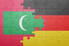 Desconcierte con la bandera nacional de Alemania y de Maldivas Imagenes de archivo
