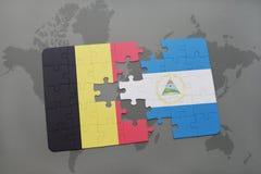 desconcierte con la bandera nacional de Bélgica y de Nicaragua en un fondo del mapa del mundo Fotografía de archivo