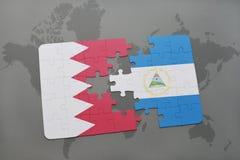 desconcierte con la bandera nacional de Bahrein y de Nicaragua en un fondo del mapa del mundo Imagenes de archivo