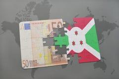 desconcierte con la bandera nacional de Burundi y del billete de banco euro en un fondo del mapa del mundo Imágenes de archivo libres de regalías