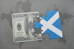 desconcierte con la bandera nacional de Escocia y del billete de banco del dólar en un fondo del mapa del mundo Foto de archivo libre de regalías