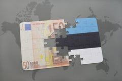 desconcierte con la bandera nacional de Estonia y del billete de banco euro en un fondo del mapa del mundo Fotos de archivo libres de regalías