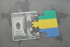 desconcierte con la bandera nacional de Gabón y del billete de banco del dólar en un fondo del mapa del mundo Fotografía de archivo libre de regalías