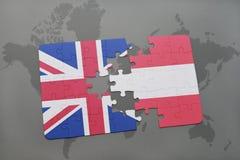 desconcierte con la bandera nacional de Gran Bretaña y de Austria en un fondo del mapa del mundo foto de archivo