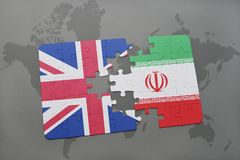 desconcierte con la bandera nacional de Gran Bretaña y de Irán en un fondo del mapa del mundo Fotografía de archivo libre de regalías