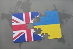 desconcierte con la bandera nacional de Gran Bretaña y de Ucrania en un fondo del mapa del mundo Fotografía de archivo libre de regalías