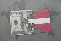 desconcierte con la bandera nacional de Letonia y del billete de banco del dólar en un fondo del mapa del mundo Fotografía de archivo
