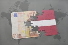 desconcierte con la bandera nacional de Letonia y del billete de banco euro en un fondo del mapa del mundo Fotografía de archivo libre de regalías