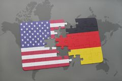 Desconcierte con la bandera nacional de los Estados Unidos de América y de Alemania en un fondo del mapa del mundo Imagenes de archivo