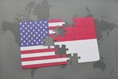 desconcierte con la bandera nacional de los Estados Unidos de América y de Indonesia en un fondo del mapa del mundo Imagen de archivo
