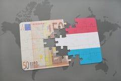 desconcierte con la bandera nacional de Luxemburgo y del billete de banco euro en un fondo del mapa del mundo Imagen de archivo libre de regalías