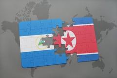 desconcierte con la bandera nacional de Nicaragua y de Corea del Norte en un mapa del mundo Foto de archivo libre de regalías
