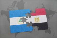 desconcierte con la bandera nacional de Nicaragua y de Egipto en un mapa del mundo Imagen de archivo libre de regalías