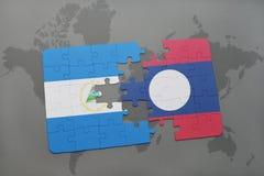 desconcierte con la bandera nacional de Nicaragua y de Laos en un mapa del mundo Imagen de archivo libre de regalías