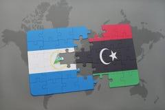 desconcierte con la bandera nacional de Nicaragua y de Libia en un mapa del mundo Foto de archivo libre de regalías