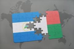 desconcierte con la bandera nacional de Nicaragua y de Madagascar en un mapa del mundo Imagen de archivo
